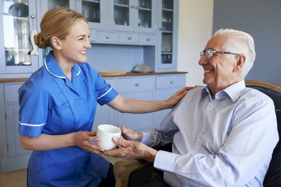 nurse giving elderly man a cup of tea