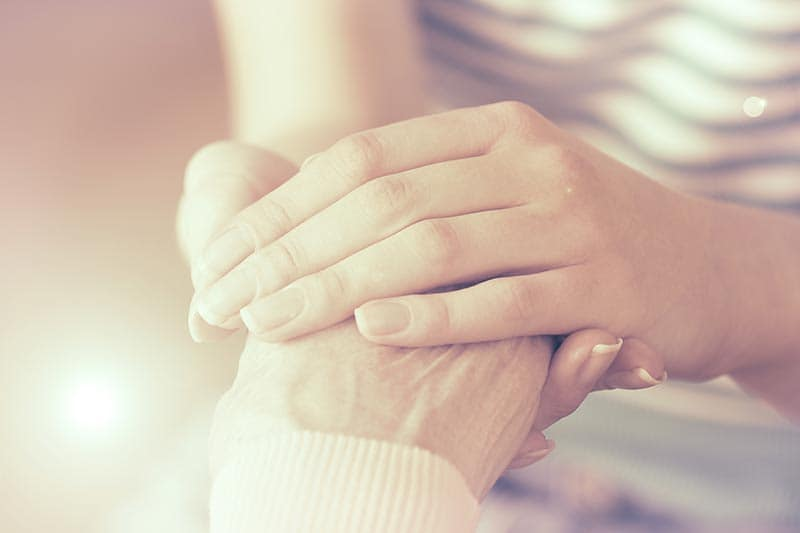 young person holding hands with old person