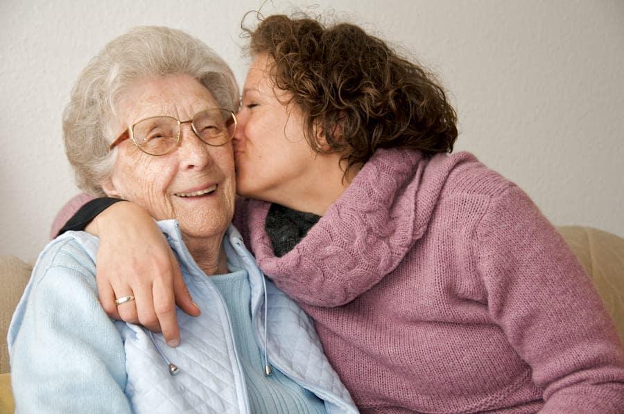 young woman giving smiling senior woman kiss on the cheek